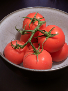 bowl of red tomatoes on vine