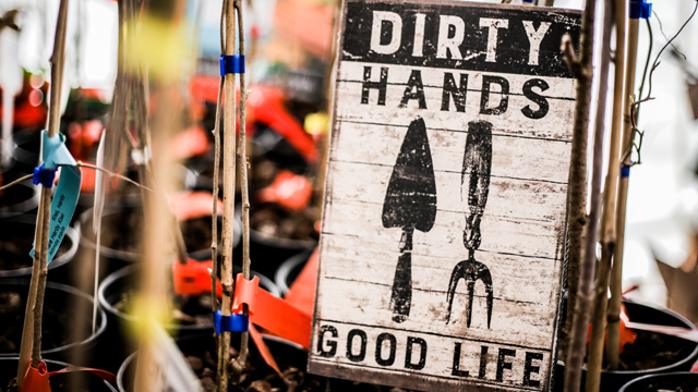 "Painted wooden sign displayed at the 24th Annual Spring Conference which says, ""Dirty Hands, Good Life"""
