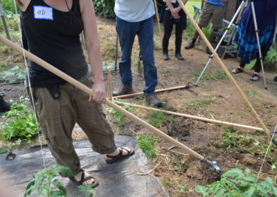 A CRAFT Tour farm participants, whose head is cut off by the camera, tests out a hoe in a garden bed