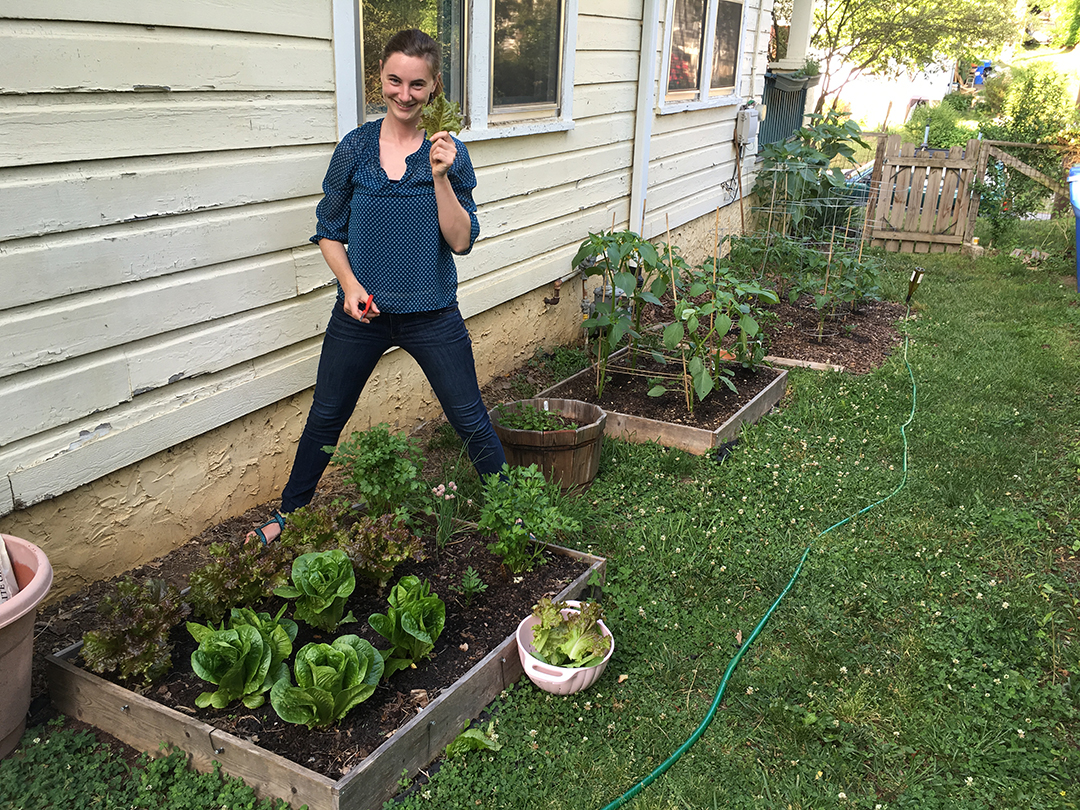 Full-body shot of a woman standing by small, boxed gardens filled with edible greens. The gardens are situated behind a house, and the woman straddles the edge of one of the boxes and smiles while holding up a lettuce leaf.