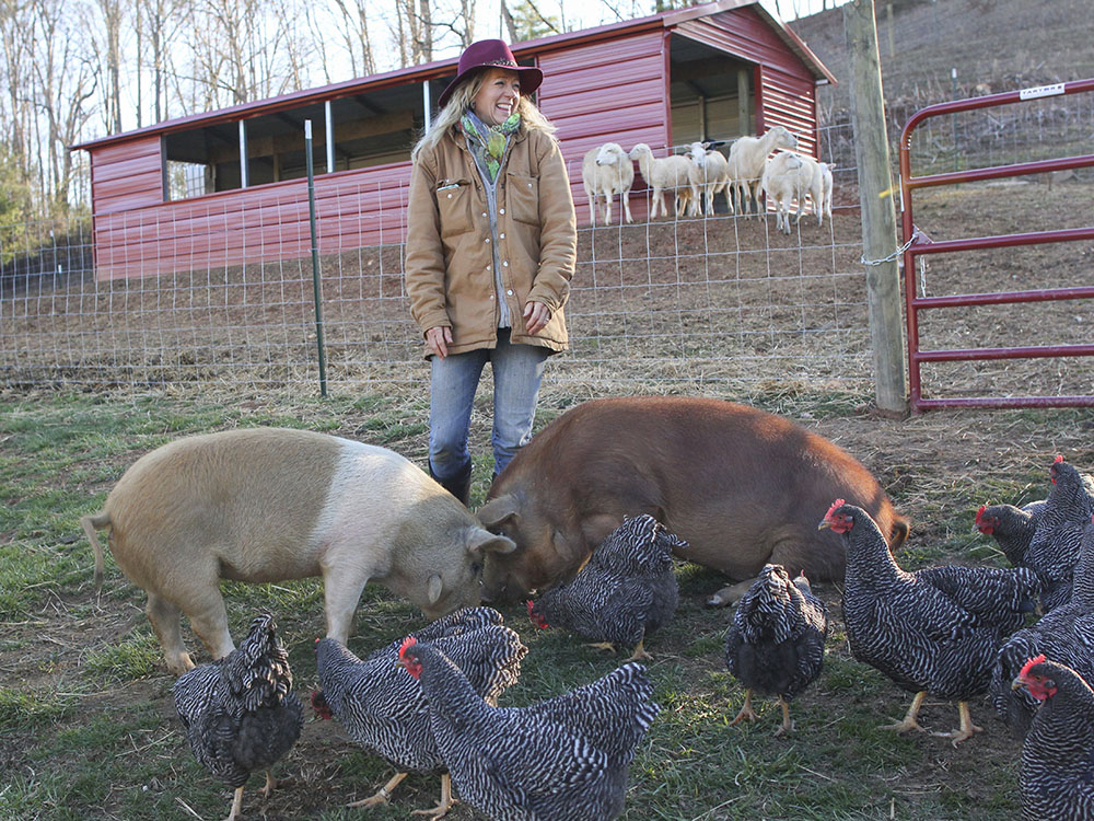 Franny Tacy stands on her farm land with pigs and chickens foraging the ground at her feet and sheep looking on from the background.