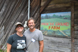 Nicole and Gaelan the farmers at Green Toe ground in front of their farm sign.