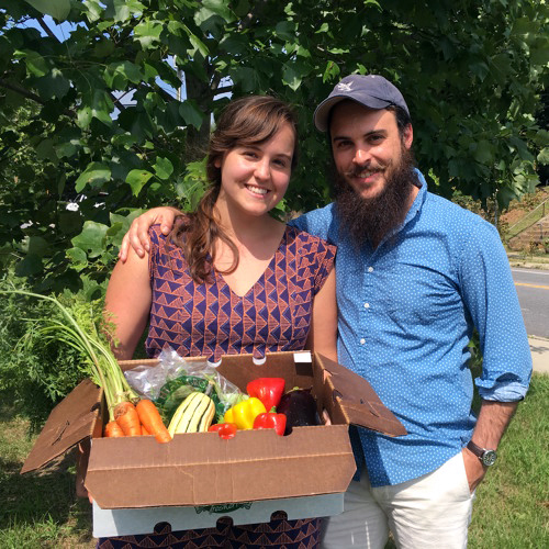 The Costlow's, Macon on the left and Luke on the right, are seen from knee up, smiling at the camera and standing on a grassy field with a tree and asphalt road behind them. Macon is holding a cardboard box filled with a variety of color vegetables, and Luke draping his right arm around Macon's shoulder.