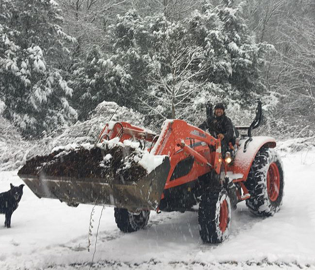 Gaelan, farmer at Green Toe Ground on the tractor in the snow.
