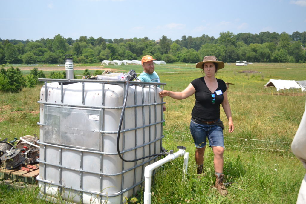 Marie stands next to a large white cube reservoir tank used for storing water the pigs.